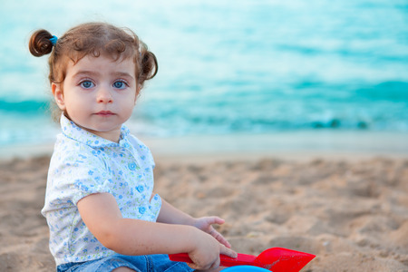 Blu eyes brunette toddler girl playing with sand in beach at mediterranean photo