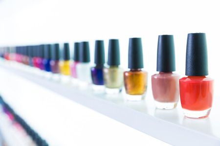 colorful nail polish colors in a row at nails saloon on white background photo