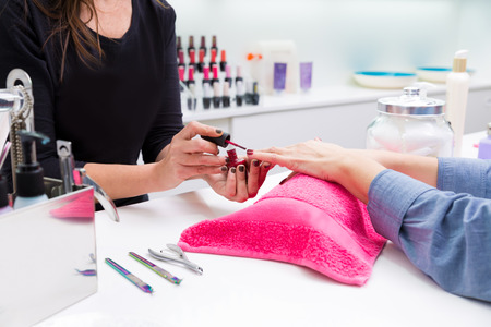 beauty saloon: Nail saloon woman painting color nail polish in hands over pillow with pink towel