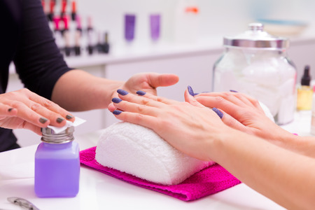 Nails saloon woman nail polish remove with tissue for new manicure photo