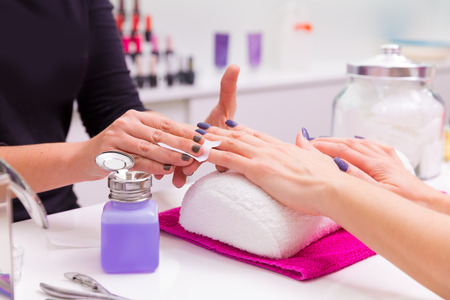 beauty saloon: Nails saloon woman nail polish remove with tissue for new manicure Stock Photo