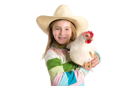 Blond kid girl farmer holding white hen on arms with cowboy hat photo