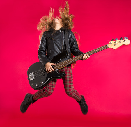 Blond Rock and roll girl jumping playing bass guitar on red background photo