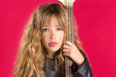 Blond Rock and roll girl bass guitar player portrait on red background photo