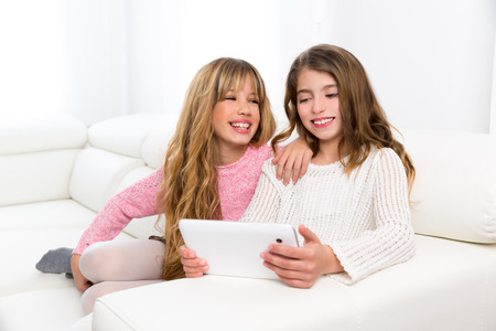 Children friends kid girls playing together with tablet pc on white sofa photo