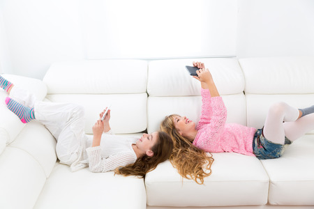 Children friends kid girls having fun playing with tablet pc lying on white sofa photo