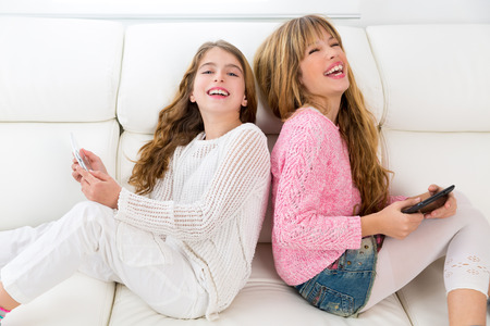 Children friends kid girls having fun playing back to back with tablet pc on white sofa photo