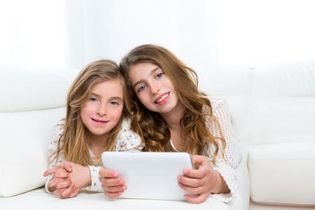 Children sister friends kid girls playing together with tablet pc lying on white sofa photo