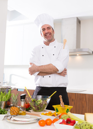 Chef male portrait on white countertop with food at kitchen photo