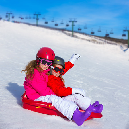 Kid girls playing sled in winter snow with helmets and goggles photo