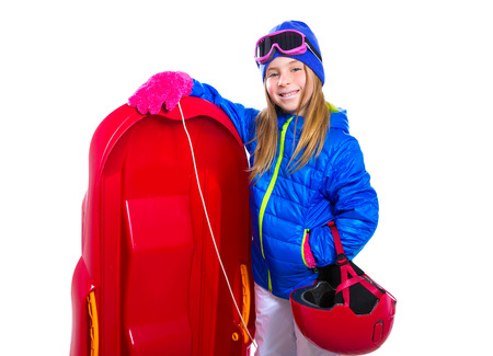 Blond kid girl with red sled and snow equipment helmet and goggles isolated on white  photo