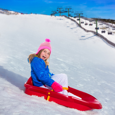 Kid girl playing sled in snow with winter wool pink hat photo