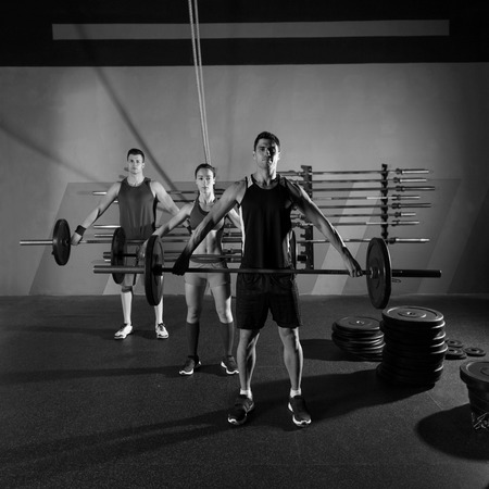 black man white woman: Barbell weight lifting group workout exercise at gym box