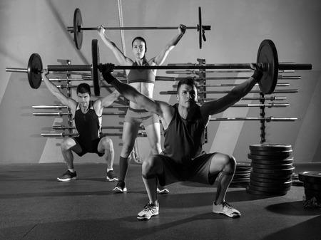 levantar pesas: Barbell del levantamiento de pesas de ejercicio de entrenamiento de grupo en la caja de gimnasio