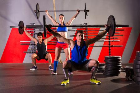 levantando pesas: Barbell del levantamiento de pesas de ejercicio de entrenamiento de grupo en la caja de gimnasio