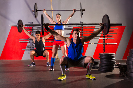 fit women: Barbell weight lifting group workout exercise at gym box