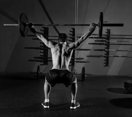 athlete: barbell weight lifting man rear view back workout exercise at gym box Stock Photo