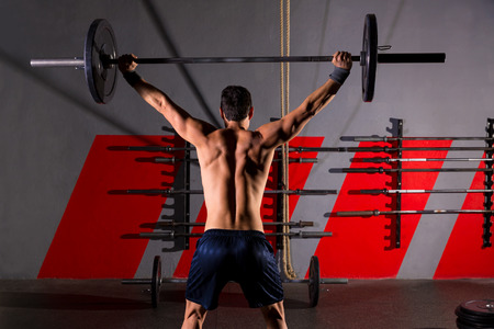 cross bar: barbell weight lifting man rear view back workout exercise at gym box Stock Photo