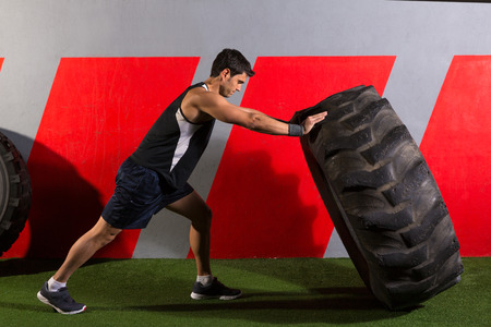 man flipping a tractor tire workout exercise at gym photo