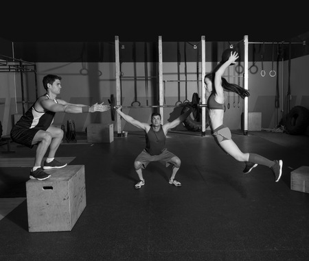 crossfit: gym people group workout barbells slam balls and jump exercises