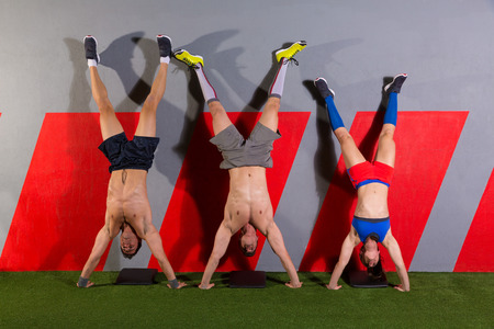 abdominal wall: Handstand push-up group pushups workout top position at gym