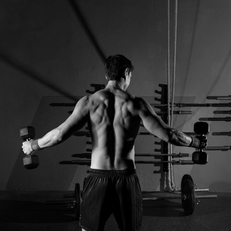 cross bar: hex dumbbells man workout rear view back exercise at gym box Stock Photo