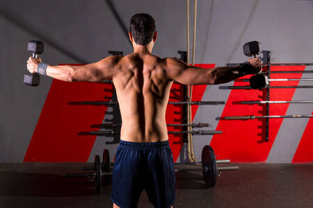back training: hex dumbbells man workout rear view back exercise at gym box Stock Photo