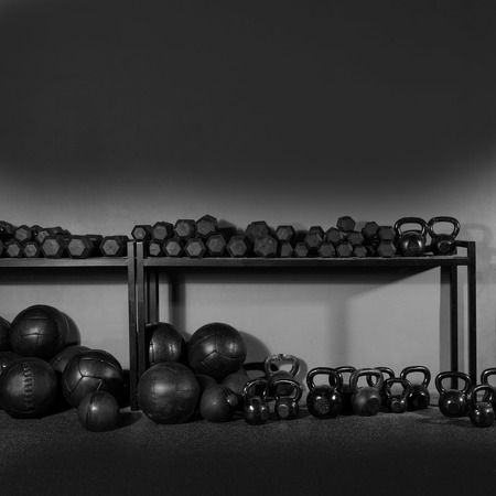 equipment: Kettlebells dumbbells and weighted slam balls weight training equipment at gym