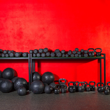gym ball: Kettlebells dumbbells and weighted slam balls weight training equipment at gym red wall Stock Photo