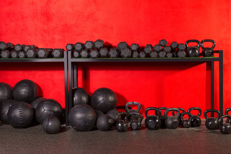 Kettlebell dumbbell and weighted slam balls weight training equipment at gym red walls photo