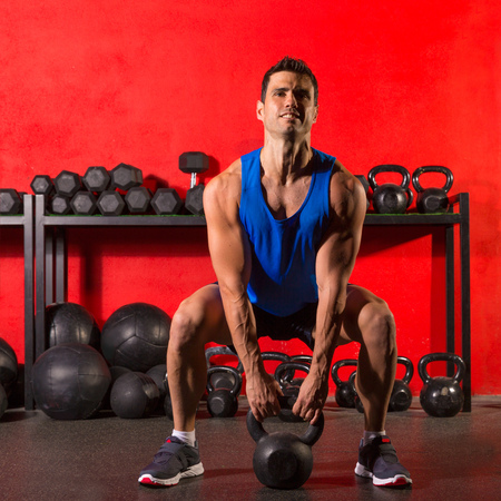 Kettlebell swing workout training man at gym with red walls photo