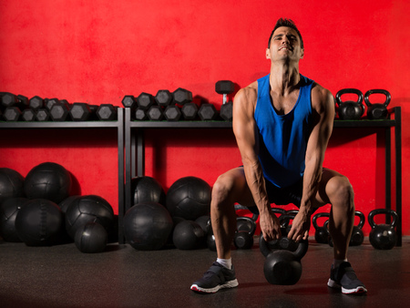 abdominal wall: Kettlebell swing workout training man at gym with red walls Stock Photo