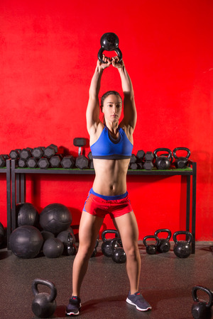 Kettlebell swing workout training woman at gym with red walls photo