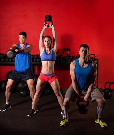 Kettlebell balançoire groupe de formation d'entraînement au gymnase avec mur rouge