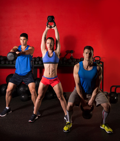 Kettlebell swing workout training group at gym with red wall photo