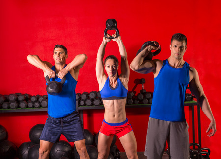 abdominal wall: Kettlebell swing workout training group at gym with red wall