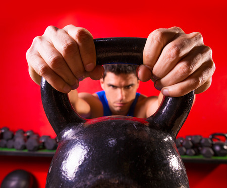 Kettlebell man portrait looking through the handle ring at gym workout photo