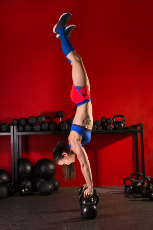 kettlebell handstand woman workout in red gym with dumbbells background photo