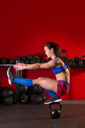 ケトルベル女性ピストルのスクワット運動バランス赤のジムで 写真素材