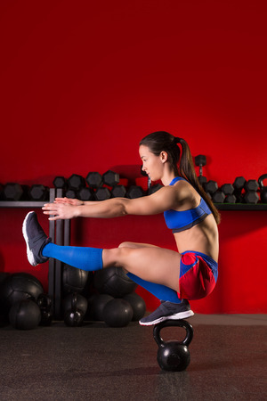 handguns: kettlebell woman pistol squat workout balance in red gym Stock Photo