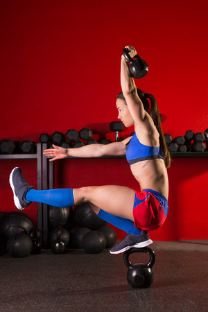abdominal wall: kettlebell woman pistol squat workout balance in red gym Stock Photo