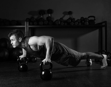 Kettlebells push-up man strength pushup exercise workout at gym photo