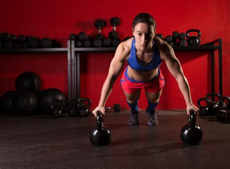 Kettlebells push-up force de femme enfoncement exercice d'entraînement au gymnase Banque d'images