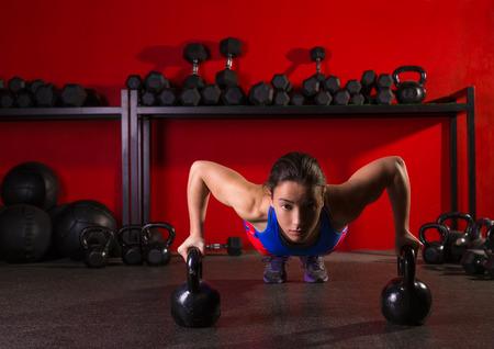 Kettlebells femme force push-up pushup exercice d'entraînement au gymnase Banque d'images