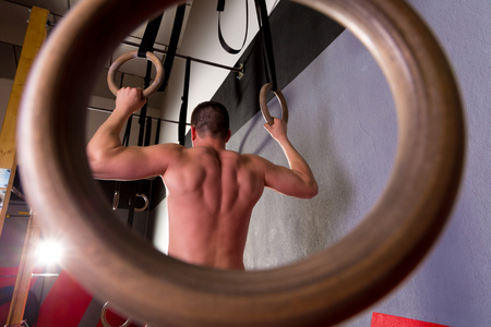 Rings workout man at gym hanging rear back view photo