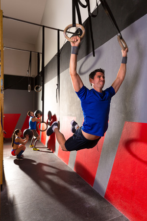 hang body: Muscle ups rings man swinging workout exercise at gym Stock Photo