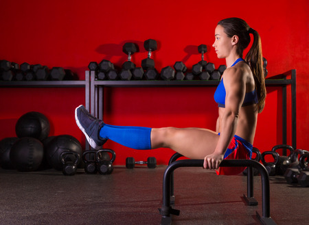 cross bar: Parallettes woman parallel bars workout exercise at red gym