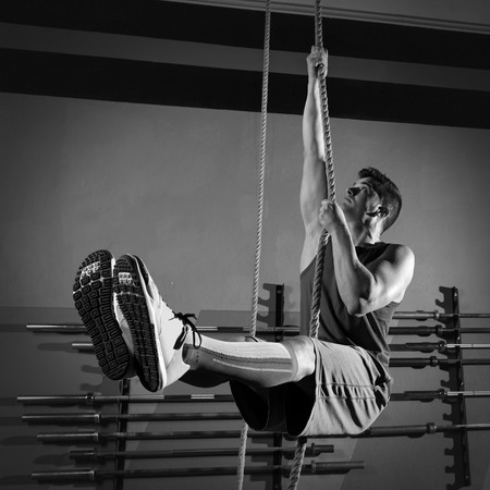 Rope Climb exercise man workout at gym climbing photo