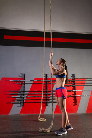 Rope Climb exercise woman workout at gym climbing photo