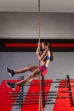 rope climb exercise woman workout at gym climbing stock photo